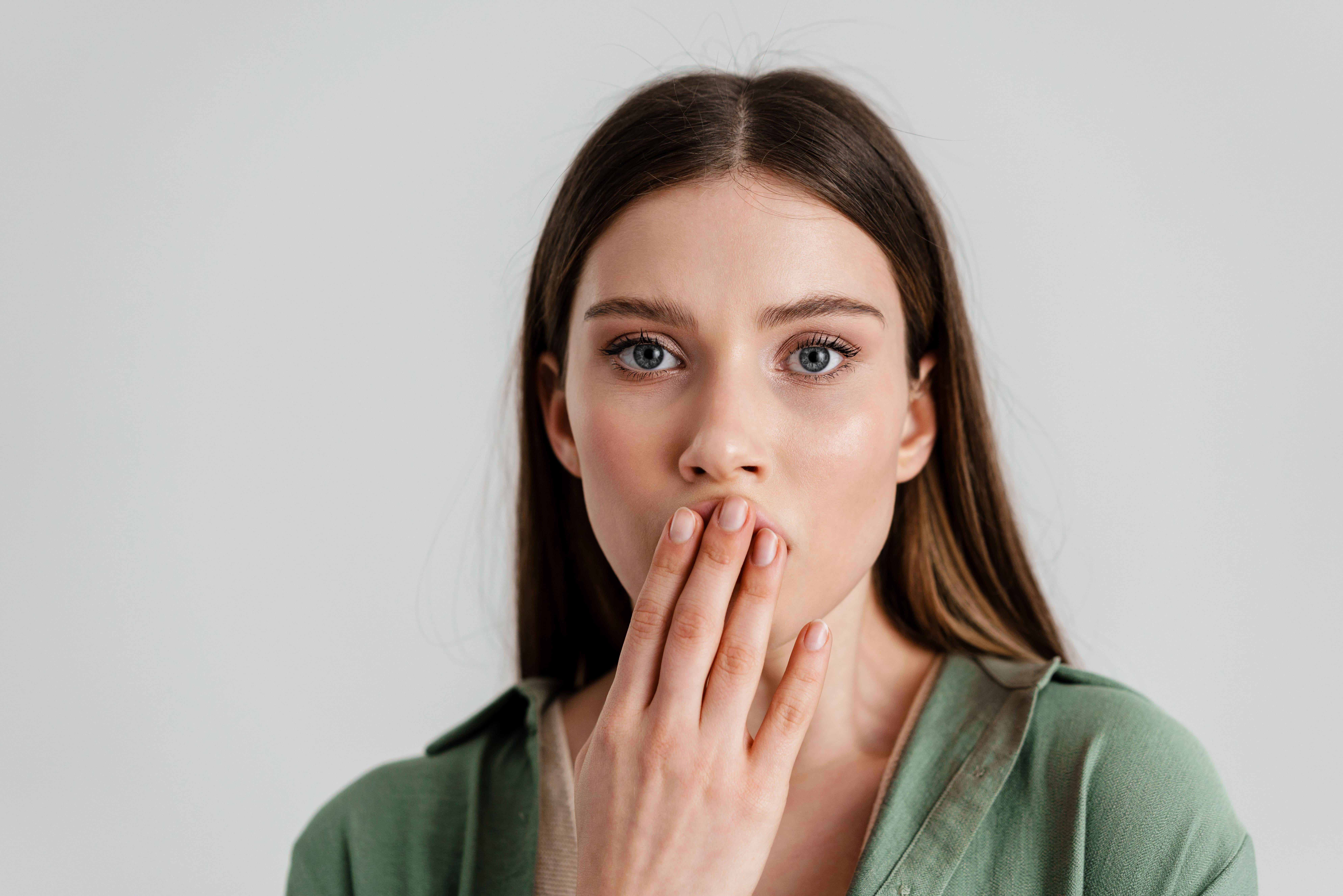 Ragazza si copre la bocca con una mano